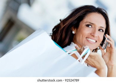 Shopping woman talking on the phone and holding bags