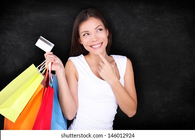 Shopping woman thinking with bags on blackboard background. Shopper girl holding credit card and shopping bag looking up at blackboard / chalkboard background with copy space. Mixed race Asian model.