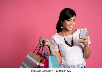 shopping woman using smartphone and hold shopping bags shoot over pink background