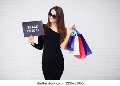 Shopping. Women holdingdiscount blanks on ligth background in black friday holiday.