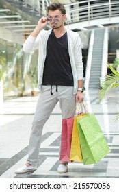 Shopping. Young handsome man with bags for shopping and glasses, in shopping center