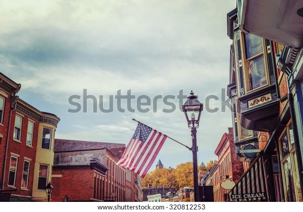 Shops along main street, Galena, Illinois, focus on flag, vintage toned image.