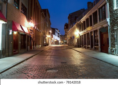 Shops and illuminated street of Old Montreal at dusk