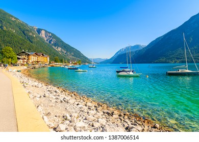 Shore of beautiful Achensee lake and boats on sunny summer day with blue sky, Karwendel mountain range, Tyrol, Austria