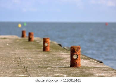 Shore of beton with few brown, old small poles, a bit corroded, lake and horiozn