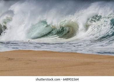 Shore break Ocean wave on the beach at Waimea Bay on the norths shore of Oahu Hawaii