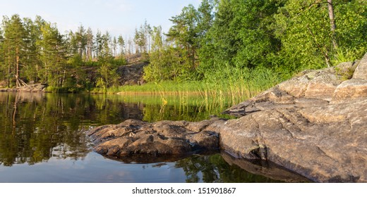 shore of forest lake with rocks, panorama