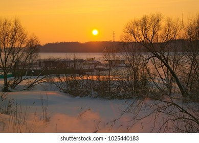 The shore and the frozen river Kostroma at sunset.