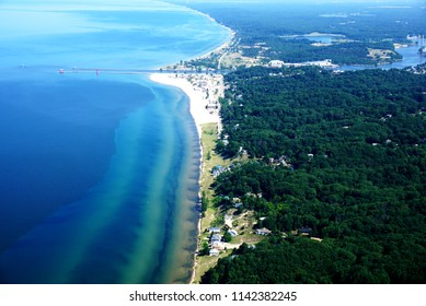 The Shore of Lake Michigan from a Bird's Eye View. Flying Plane. Coastline. Green Forests, Rivers and Houses. Transparent Blue Water. Two Lighthouses on Long Piers. Embankment of Grand Haven, Michigan