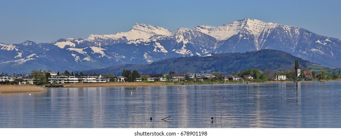 Shore of lake Zurich and snow capped mountain Grosser Speer, Switzerland
