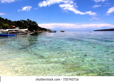 The shore of Samal Island in the Philippines with crystal clear waters, docked boats and a clear blue sky.