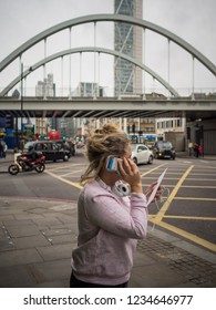 SHOREDITCH, LONDON, ENGLAND, 17 OCT, 2014 - A woman speaks into her cellphone on the corner of a street in Shoreditch, London.
