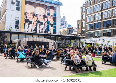 Shoreditch, London, England, UK - April 2019: Pop up Outdoor food area with people eating outiside and big mural street art celebrating Andy Warhol at The Old Truman Brewery, Ely's Yard, Shoreditch