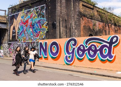 "Shoreditch, London, UK - April 18 2015: Three hipster girls walking in front of a wall covered in graffiti with the writing ""No Good"". Shoreditch is home of some of the world's best street art."