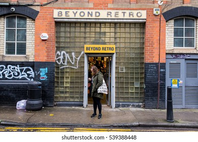 Shoreditch, London, UK - January 24 2016:  Young woman checking the phone in front of the entrance of Beyond Retro, a huge vintage clothing store situated just off Brick Lane, Shoreditch, East London