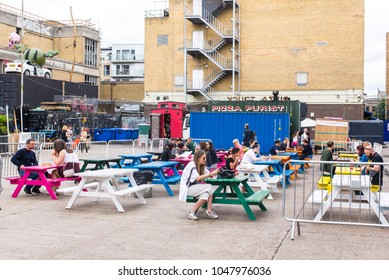 Shoreditch, London, UK - June 2017: Pop up outdoor restaurants with people eating outiside at The Old Truman Brewery, Ely's Yard, Shoreditch, London, UK
