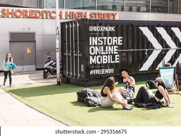 Shoreditch, London, UK - June 28 2015: Group of young hipsters sitting down on a fake grass carpet in the Boxpark, the world's first pop-up mall. Based in Shoreditch, East London.