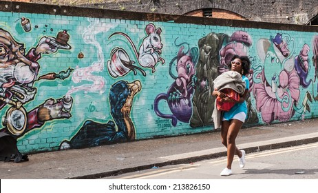 SHOREDITCH, LONDON, UK, June 8 2014: Street art in Shoreditch. Black woman walking holding her son, in front of  on a wall decorated in graffiti in Shoreditch.
