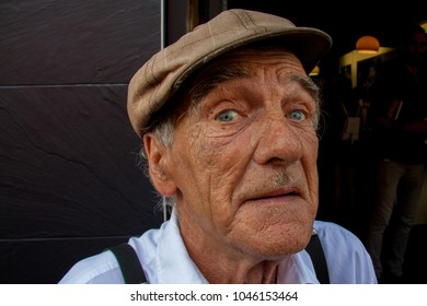 Shoreditch, London, UK - September 28 2014 : Portrait of an old East End character with pale blue eyes, brown weathered skin wearing a flat cap and braces, in Brick Lane, London
