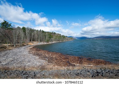 Shoreline and Distant Mountains at the Ashokan Reservoir. Beautiful Spring Morning, Blue Sky with Clouds and Driftwood and Stone Wall along the shore. NYC Water Supply and Tourist Destination.