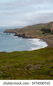 Shoreline at Rodeo Beach, California, USA, in Sausalito's Marin Headlands recreation area on a partly cloudy sky with lots of copy space- long exposure and vertical composition