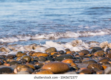 The shoreline of South Carlsbad State Beach in San Diego, California, with waves and stones covering the beach.