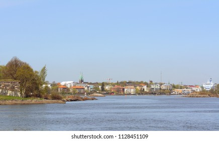 Shoreline of Suomenlinna, a UNESCO World Heritage site in Finland, lined with houses, buildings and trees
