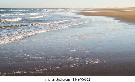 Shoreline with waves lapping the sand on a clear sunny day at Bamburgh, England UK.