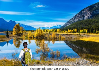 Shores of Abraham Lake in the Rocky Mountains of Canada. Middle-aged woman with a large green tourist backpack admires the lake. Concept of active, ecological and photo tourism