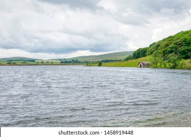 The shores of Malham Tarn with darkening clouds approaching. Viewed from the Pennine Bridleway