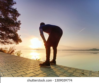Short break for breath. Silhouette of active man exercising and stretching on the lake beach at sunrise. Healthy lifestyle.