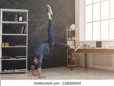 Short break for yoga in office. Flexible man practicing yoga at workplace, making stretching exercise while using tablet, copy space. Active employee at work, healthy lifestyle concept