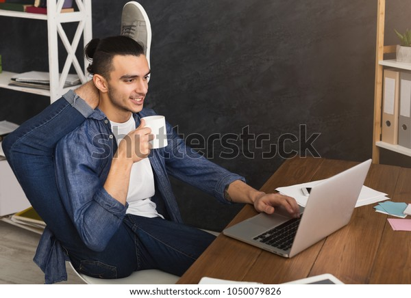 Short break for yoga in office. Flexible man practicing yoga at workplace, while typing on laptop and having coffee, copy space. Active employee at work, healthy lifestyle concept