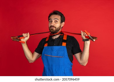 Short circuit. Funny young bearded man, male auto mechanic or fitter wearing blue work dungarees isolated over red studio background. Concept of funny meme emotions, ad, job, insipation, ideas, sales