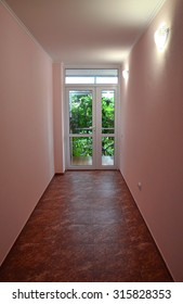 Short corridor with the pink walls and brown tile floor. Simple hallway towards a yard, with the glazed door and wall lamps. Corridors and passageways under artificial lighting