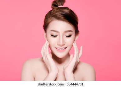 Short hair asian young beautiful woman smiling and touching her face, isolated over pink background. natural makeup, SPA therapy, skincare, cosmetology and plastic surgery concept