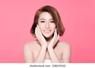 Short hair asian young beautiful woman smile and touch her face, isolated over pink background. natural makeup, SPA therapy, skincare, cosmetology and plastic surgery concept
