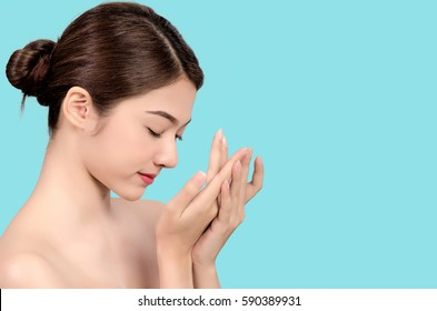 Short hair asian young beautiful woman smiling and touching her face, isolated over blue background. natural makeup, SPA therapy, skincare, cosmetology and plastic surgery concept