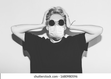 Short hair girl in corona virus protective medicine mask and sunglasses saving her from infection holding her head. Black and white toned style with crazy woman in black t-shirt.