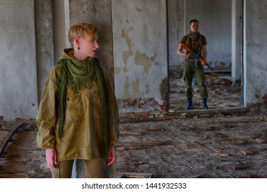Short hair girl is hiding from a man in military clothes with a machine gun weapon (soldier, murderer, maniac or kidnapper) in an abandoned building. The scene of a violence or war or in trouble.