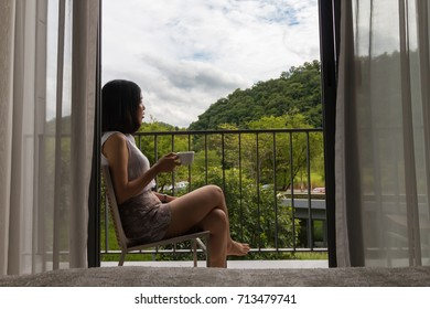 a short hair young woman sitting at the balcony with a cup of coffee and enjoying the beautiful of nature