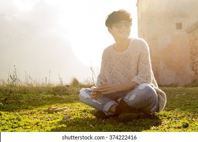 short haired brunette girl is sitting on the lawn wearing a jumper and a pair of jeans