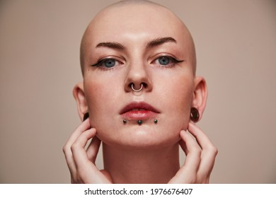 Short haired naked woman with piercing at her face looking straight while posing