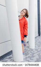 A short haired woman in coral windbreaker and colorful socks hiding behind a column near grey wall