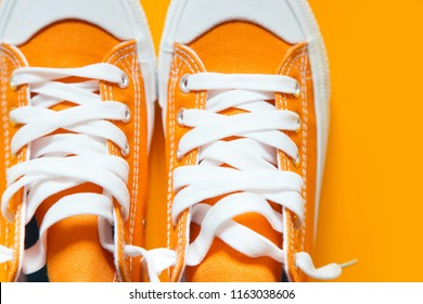 Short low  bright sneakers on a orange background.