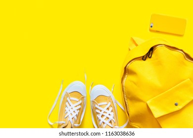 Short low  bright sneakers on a yellow background. Backpack, pho