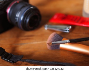 Short makeup brush, blurred nail clippers, cream cosmetic, beauty tools, black camera with straps on red brown wooden texture table top background, perspective, to prepare as a photo-shooting model