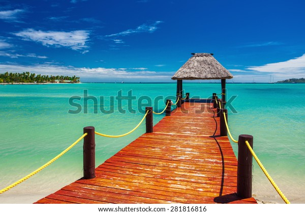 Short red wooden jetty extending to tropical ocean on Fiji Island