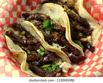 Short Rib Tacos: Korean style (bulgogi) short ribs, meat off the bone in taco shells on red checked paper.