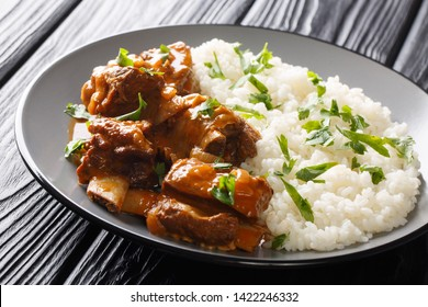 short ribs cooked in a spicy sauce with rice garnish close-up on a plate on the table. horizontal